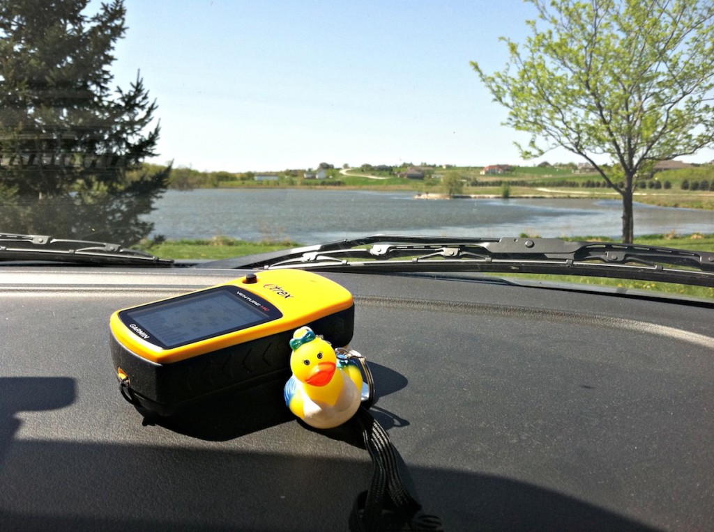 This is our GPS and a tracking bug (a trackable item that has a mission and is replaced in another cache rather than keeping it). The background is a local lake we got to visit to find a cache. It was a great family outing!